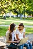 Deux amis féminins en parc se reposant sur le banc et travaillant au lapto Photo stock
