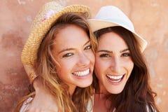 Deux amis féminins en vacances posant ensemble par le mur Photos stock