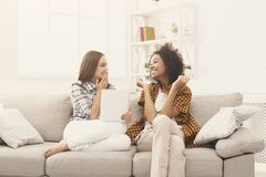 Deux amis féminins enthousiastes heureux à l'aide du comprimé Photographie stock