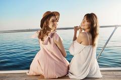 Deux amis féminins européens mignons s'asseyant sur le côté du bateau, revenant pour regarder l'appareil-photo tout en souriant l Photos stock