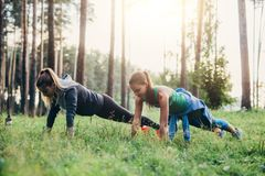 Deux amis féminins faisant la pompe exercent la formation dehors dans la forêt Image stock