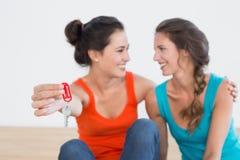 Deux amis féminins gais avec des clés de maison Photos stock