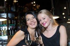 Deux amis féminins grillant dans une boîte de nuit Images libres de droits