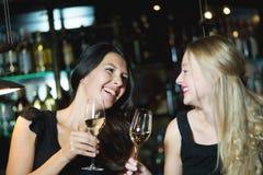 Deux amis féminins grillant dans une boîte de nuit Images stock