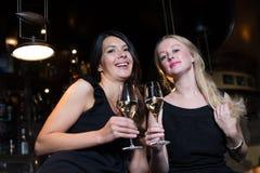 Deux amis féminins grillant dans une boîte de nuit Photo libre de droits