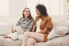 Deux amis féminins heureux à l'aide du comprimé Image stock