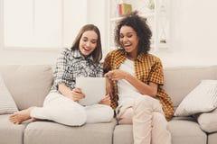Deux amis féminins heureux à l'aide du comprimé Photo stock