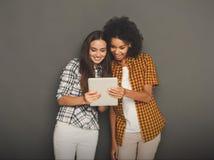 Deux amis féminins heureux à l'aide du comprimé numérique Photographie stock