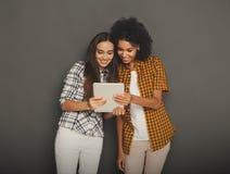 Deux amis féminins heureux à l'aide du comprimé numérique Photographie stock libre de droits