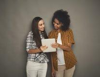 Deux amis féminins heureux à l'aide du comprimé numérique Photos stock