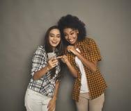 Deux amis féminins heureux à l'aide du smartphone Photo libre de droits