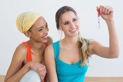 Deux amis féminins heureux avec des clés de maison Photographie stock libre de droits