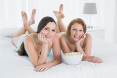 Deux amis féminins heureux avec le bol de maïs éclaté se situant dans le lit Image stock