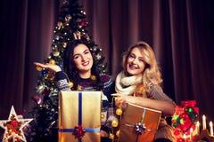 Deux amis féminins heureux ayant l'amusement devant l'arbre de Noël Image stock