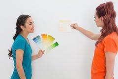 Deux amis féminins heureux choisissant la couleur pour peindre une salle Photo stock