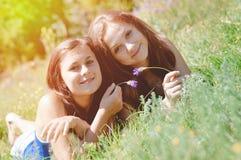 Deux amis féminins heureux jouant dans l'herbe verte Image stock