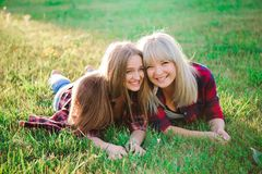 Deux amis féminins heureux jouant et ayant l'amusement dans l'herbe verte image libre de droits