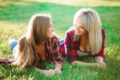 Deux amis féminins heureux jouant et ayant l'amusement dans l'herbe verte photos libres de droits