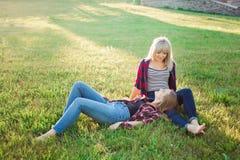 Deux amis féminins heureux jouant et ayant l'amusement dans l'herbe verte photo libre de droits