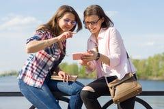 Deux amis féminins heureux observant les photos, vidéos sur le smartphone et ayant l'amusement Photo stock