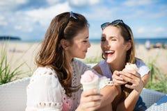 Deux amis féminins heureux s'asseyant en dehors de tenir la crème glacée  Image libre de droits