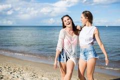 Deux amis féminins heureux se tenant ensemble sur rire de plage Photo stock