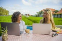 Deux amis féminins heureux travaillant dehors au beau café d'Internet avec la femme caucasienne d'ordinateur portable et une fill Photographie stock libre de droits