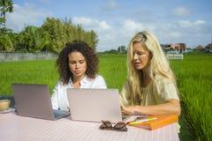 Deux amis féminins heureux travaillant dehors au beau café d'Internet avec la femme caucasienne d'ordinateur portable et une fill Photographie stock