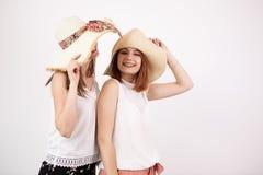 Deux amis féminins heureux utilisant des chapeaux d'été Images stock