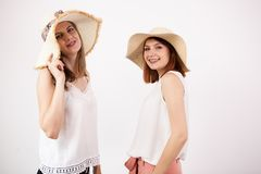 Deux amis féminins heureux utilisant des chapeaux d'été Photos stock