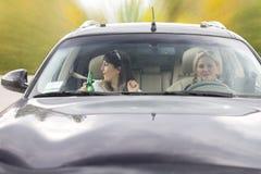 Deux amis féminins ivres conduisant une voiture Image stock