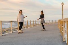 Deux amis féminins jouant avec la planche à roulettes Images libres de droits
