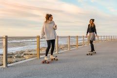 Deux amis féminins jouant avec la planche à roulettes Image libre de droits