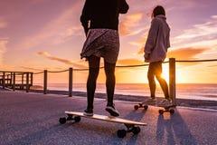 Deux amis féminins jouant avec la planche à roulettes Photographie stock libre de droits