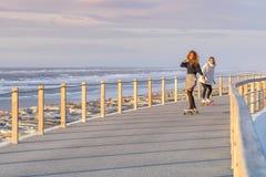 Deux amis féminins jouant avec la planche à roulettes Photos libres de droits