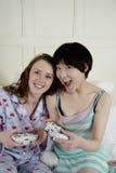 Deux amis féminins jouant le jeu vidéo Photographie stock libre de droits
