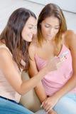 Deux amis féminins lisant le message textuel Image libre de droits