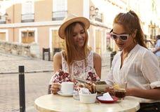 Deux amis féminins lisant un guide en dehors d'un café, Ibiza Image libre de droits