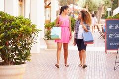 Deux amis féminins marchant le long de la rue avec des paniers Photos stock