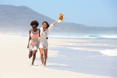 Deux amis féminins marchant nu-pieds sur la plage Image libre de droits