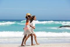 Deux amis féminins marchant sur la plage ensemble Photo libre de droits