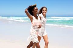 Deux amis féminins marchant sur la plage ensemble Photographie stock