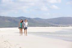Deux amis féminins marchant sur la plage vide ensemble Photo libre de droits