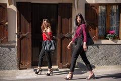 Deux amis féminins marchent le long de la rue photo libre de droits