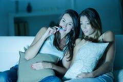 Deux amis féminins observant le film effrayant Image libre de droits