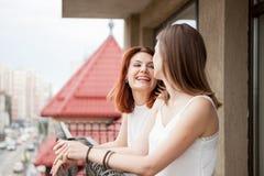 Deux amis féminins parlant et riant du balcon Image libre de droits