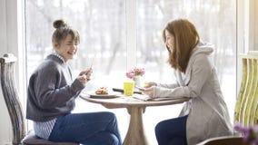 Deux amis féminins parlant rire dans un café Images libres de droits