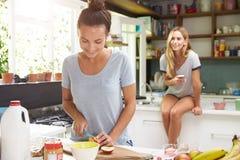 Deux amis féminins préparant le petit déjeuner à la maison ensemble Image stock