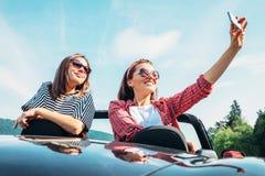 Deux amis féminins prennent une photo de selfie dans la voiture de cabriolet pendant le t Photographie stock