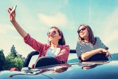 Deux amis féminins prennent une photo de selfie dans la voiture de cabriolet pendant le t Photographie stock libre de droits